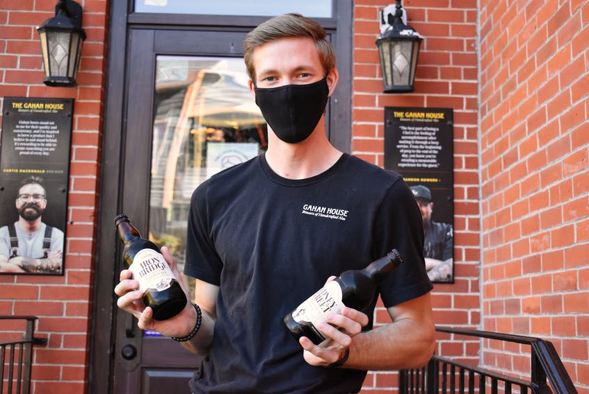 Ryan Dutton, a server at the Gahan House in Charlottetown, holds two bottles of Gahan beer. Due to a bottle shortage, the P.E.I. Brewing Company is halting bottle production of their Gahan line of beers, though all products will still be available in other formats.
