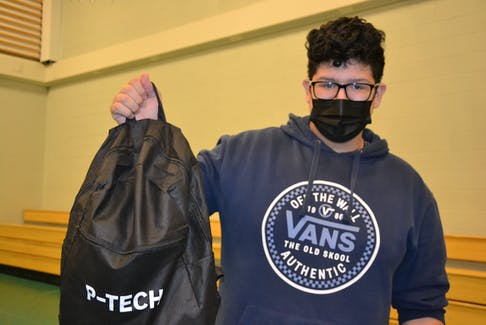 Grade 11 student Kaisa'n Stevens holds up his P-Tech branded backpack from IBM Canada at the announcement of the Unama'ki P-Tech school at Allison Bernard Memorial High School on Tuesday. Stevens said he enrolled in the program because he's interested in engineering and hopes to be a nuclear engineer in the future. ARDELLE REYNOLDS/CAPE BRETON POST