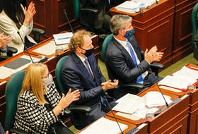 Nova Scotia Premier Tim Houston, right, watches with MLAs Karla MacFarlane, left, and Allan MacMaster as Lt.-Gov. Arthur LeBlanc reads the speech from the throne at Province House in Halifax on Tuesday, Oct. 12, 2021.