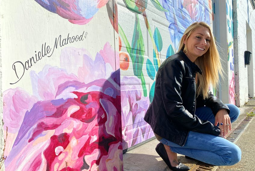 Danielle Mahood by her Jenesis Interiors mural on Water Street. CARLA ALLEN • TRI-COUNTY VANGUARD