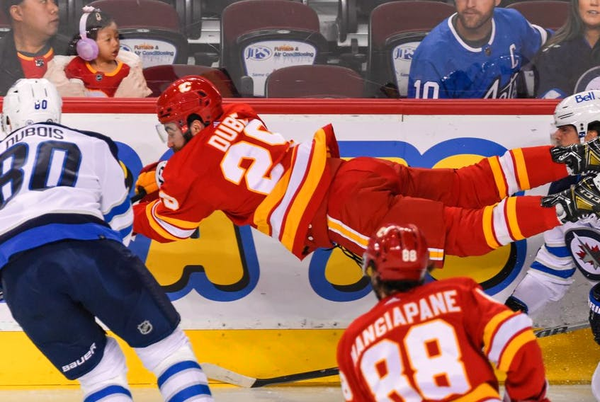 Calgary Flames forward Dillon Dube gets airborne as he fights for the puck against the Winnipeg Jets during Friday's preseason finale at the Scotiabank Saddledome.