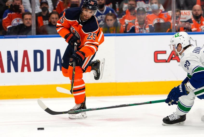 Edmonton Oilers' Darnell Nurse (25) shoots past Vancouver Canucks' Oliver Ekman-Larsson (23) during first period NHL action at Rogers Place in Edmonton, on Wednesday, Oct. 13, 2021.