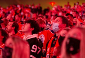 Hockey fans sing the national anthem as the Edmonton Oilers play the Vancouver Canucks during NHL action at Rogers Place in Edmonton on Wednesday, Oct. 13, 2021.