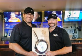 Quentin Gillis, left, owner-operator of Holy Cow, and chef Aaron Ferrill hold the winner's plaque after their burger, The Lone Ranger, was named the winner of the 2021 P.E.I. Burger Love campaign. Gillis said despite a few issues, the campaign was a success for them. Contributed