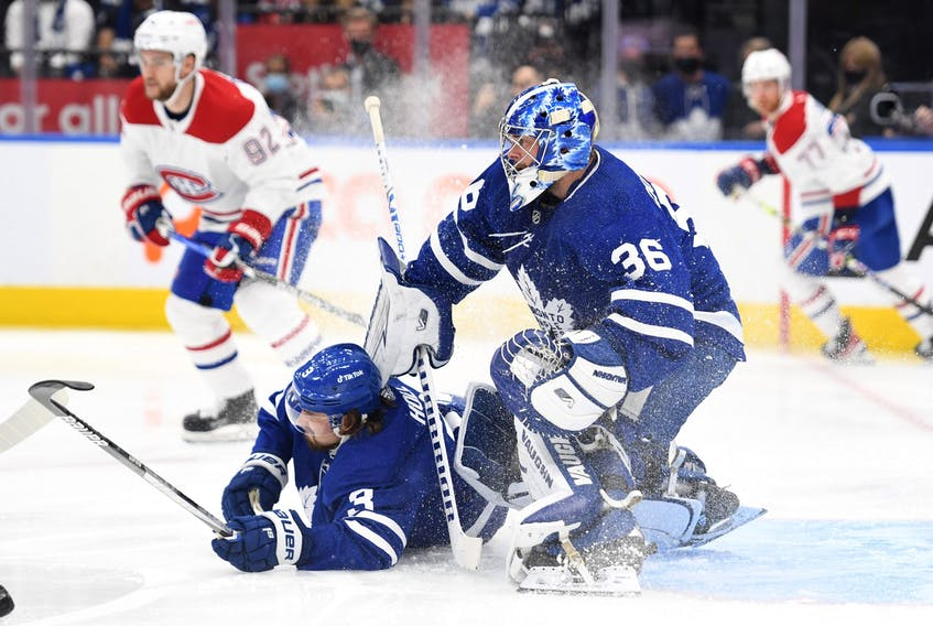 Maple Leafs' Justin Holl falls to the ice in front of goalie Jack Campbell in the first period against Montreal Canadiens at Scotiabank Arena on Wednesday, Oct. 13, 2021.