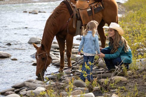 In the Season 15 opener on Heartland, Amy (Amber Marshall) and Lyndy (played by twins Ruby and Emmanuella Spencer) ride to the stream. Courtesy, Heartland Season 15.