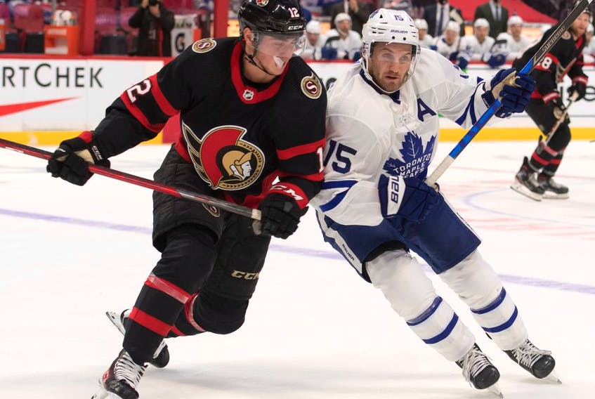 Senators centre Shane Pinto (12) battles with Maple Leafs centre Alexander Kerfoot in the first period of a pre-season game on Oct. 4.