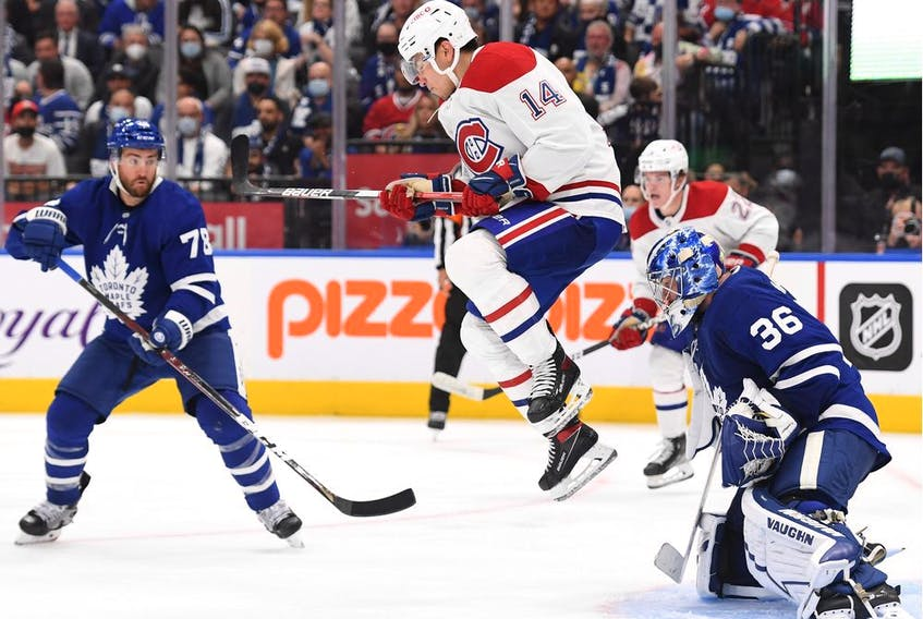 Canadiens forward Nick Suzuki tries to screen Leafs goalie Jack Campbell as T.J. Brodie, left, looks on Wednesday night at Scotiabank Arena.