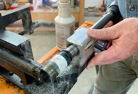 A drill in action spinning a hole saw that's shaping the end of a black iron pipe. By notching the end like this it can meet flawless with adjoining pipes that form a railing or cage.