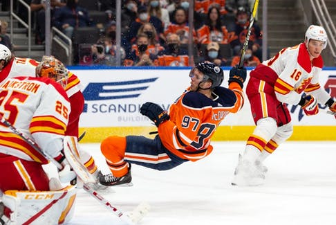The Edmonton Oilers' Connor McDavid collides with Calgary Flames goaltender Jacob Markstrom during preseason action at Rogers Place in Edmonton on Monday, Oct. 4, 2021.
