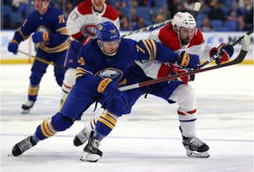 Sabres' Rasmus Asplund, left, battles Canadiens' Cedric Paquette for a loose puck during first period at KeyBank Arena Thursday night.