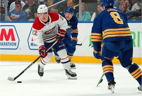 Cole Caufield of the Montreal Canadiens skates up ice with the puck as Mark Pysyk of the Buffalo Sabres and Robert Hagg, right, defend during the third period at KeyBank Center on Oct. 14, 2021, in Buffalo.