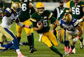 Edmonton Elks quarterback Taylor Cornelius (15) runs the ball past Winnipeg Blue Bombers defensive end Willie Jefferson (5) and Jackson Jeffcoat (94) at Commonwealth Stadium in Edmonton on Friday, Oct. 15, 2021.
