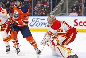 Edmonton Oilers forward Brendan Perlini (42) looks for a puck in front of Calgary Flames goaltender Jacob Markstrom (25) during the first period at Rogers Place.