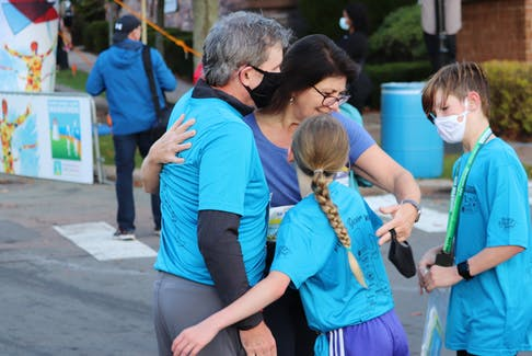 A runner hugs her supporters after finishing one of Saturday, Oct. 16's events at the 2021 P.E.I. Marathon. The Marathon weekend runs from Oct. 15-17.