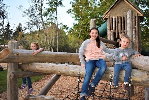 Local youngsters Charlee Winter (left), and Danica and Gavin Hebert, enjoy the 'log run', which is part of the new Portapique Community Hall playground.