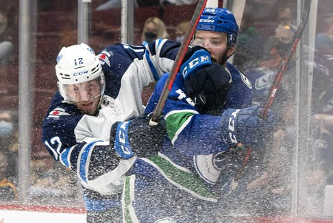 Vancouver Canucks' Kyle Burroughs (right) is checked into the end board by Winnipeg Jets' Jansen Harkins during third period NHL preseason hockey action in Vancouver, Sunday, Oct. 3, 2021.