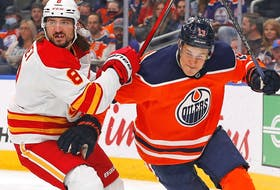 Calgary Flames defencemen Chris Tanev and Edmonton Oilers forward Jesse Puljujarvi battle for a loose puck during pre-season action at Rogers Place in Edmonton on Oct. 4, 2021.