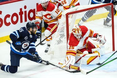 Calgary Flames goalie Jacob Markstrom clears the puck away from Winnipeg Jets forward Matthieu Perreault during the third period at Bell MTS Place in Winnipeg on Thursday, Jan. 14, 2021.