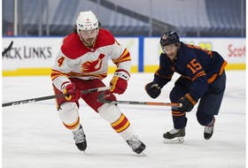 Edmonton Oilers Josh Archibald (15) and Calgary Flames Rasmus Andersson (4) skate for the puck during second period NHL action on Saturday, May 1, 2021 in Edmonton.