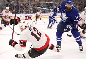 Maple Leafs defenceman Jake Muzzin (8) knocks Ottawa Senators forward Shane Pinto (12) over during the first period at Scotiabank Arena on Saturday.