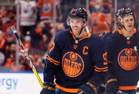Edmonton Oilers' Connor McDavid (97) celebrates a goal on Calgary Flames goaltender Jacob Markstrom (25) with teammates during second period NHL action at Rogers Place in Edmonton, on Saturday, Oct. 16, 2021.