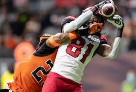 The Calgary Stampeders' Luther Hakunavanhu makes a touchdown reception as the BC Lions' Jalon Edwards-Cooper defends at BC Place in Vancouver on Saturday, Oct. 16, 2021.