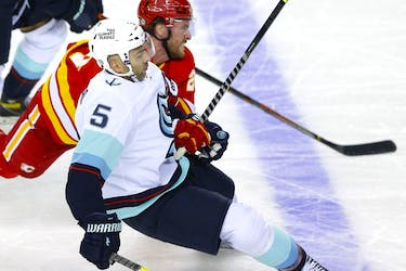The Calgary Flames' Blake Coleman battles the Seattle Kraken's Mark Giordano in pre-season action at the Scotiabank Saddledome in Calgary on Wednesday, Sept. 29, 2021.