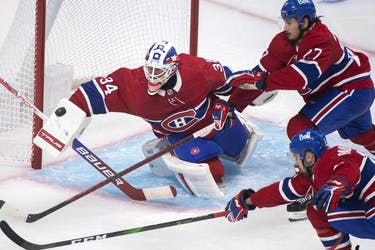 Canadiens goaltender Jake Allen makes a save against the New York Rangers as Canadiens' Alexander Romanov (27) and Cedric Paquette (13) look for the rebound at the Bell Centre in Montreal on Saturday, Oct. 16, 2021.