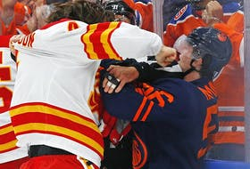 Calgary Flames defencemen Rasmus Andersson fights Edmonton Oilers forward Kailer Yamamoto at Rogers Place in Edmonton on Saturday, Oct. 16, 2021.