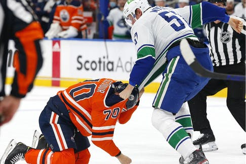 Oct 13, 2021; Edmonton, Alberta, CAN; Vancouver Canucks defensemen Tyler Myers (57) and Edmonton Oilers forward Colton Scevior (70) fight during the second period at Rogers Place.