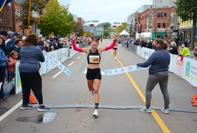 Rachel Barich raises her arms in the air as she crosses the finish line In the Prince Edward Island Marathon on Oct. 16. Barich, the top female runner in the 42.2-kilometre full marathon, had a time of two hours 56 minutes 55 seconds (2:56:55).