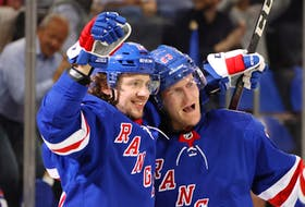 Artemi Panarin #10 of the New York Rangers (L) celebrates a second period goal by Adam Fox #23 (R) against the Dallas Stars at Madison Square Garden on October 14, 2021 in New York City.