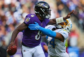 Quarterback Lamar Jackson #8 of the Baltimore Ravens stiff arms outside linebacker Kyzir White #44 of the Los Angeles Chargers during the first half  on October 17, 2021 in Baltimore, Maryland.