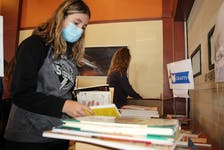 Summerside Intermediate student Callie MacDougall helps sort the books that were donated for the Summerside Rotary Book Drive for Literacy.