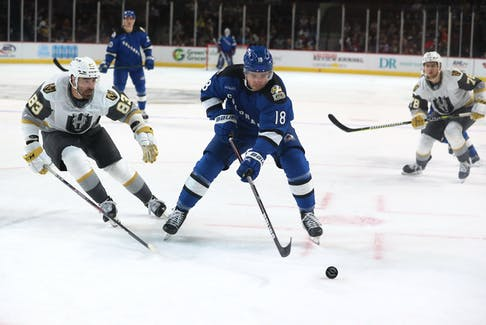 The Colorado Eagles' Alex Newhook (18) moves the puck ahead of Henderson Silver Knights defenceman Brandon Hickey (83) during an AHL game in Henderson, Nev., Sunday. — Henderson Silver Knights photo
