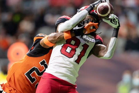 The Calgary Stampeders' Luther Hakunavanhu makes a touchdown reception as the B.C. Lions' Jalon Edwards-Cooper defends at BC Place in Vancouver on Saturday, Oct. 16, 2021.