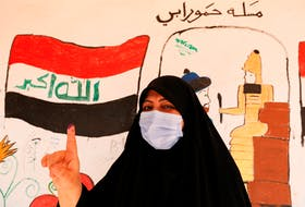 An Iraqi woman shows her ink-stained finger after casting her vote at a polling station during the parliamentary election in Sadr city, Baghdad, Iraq, on Oct. 10. Wissam Al-Okaili / REUTERS