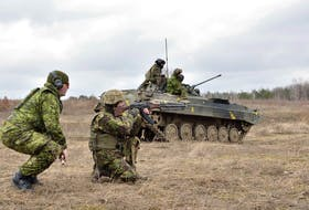 A Canadian Forces instructor provides guidance and safety support to a Ukrainian soldier during section attack practice as part of small team training, at the International Peacekeeping and Security Centre in Starychi, Ukraine, on March 3, 2017.