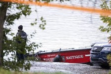 Montreal police investigate the scene Monday, October 18, 2021 after firefighter Pierre Lacroix was killed during a rescue operation on the Lachine Rapids.