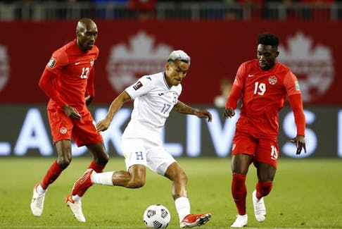 Andy Najar (No. 17) of Honduras dribbles the ball as Atiba Hutchinson (No. 13) and Alphonso Davies (No. 19) of Canada defend during a 2022 World Cup Qualifying match at BMO Field on September 2, 2021 in Toronto.