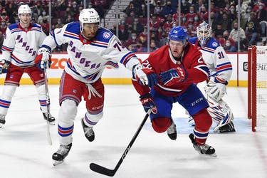 K'Andre Miller of the New York Rangers and Christian Dvorak  of the Montreal Canadiens skate after the puck during the second period at the Bell Centre on Oct. 16, 2021.