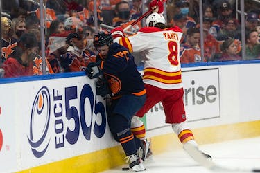 Edmonton Oilers' Kailer Yamamoto (56) battles Calgary Flames Christopher Tanev (8) during first period NHL action at Rogers Place in Edmonton, on Saturday, Oct. 16, 2021.