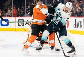 Seattle Kraken centre Riley Sheahan (15) controls the puck in front of Philadelphia Flyers defenceman Justin Braun