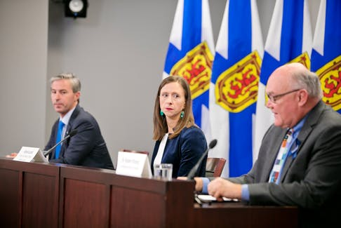 Nova Scotia Premier Tim Houston and Alyson Lamb, executive director of Nova Scotia Health's western zone, listen as Dr. Robert Strang, the province's chief medical officer of health, speaks at a COVID-19 briefing in Halifax on Tuesday, Oct. 19, 2021.