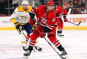 Carolina Hurricanes' Jesperi Kotkaniemi skates the puck away from Nashville Predators' Yakov Trenin during the second period in Raleigh, N.C., on Oct. 5, 2021.