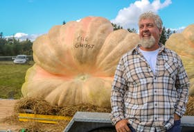 Carl Graham stands beside his prize pumpkin, Howard the Ghost, which weighed in at 1,956 pounds, an Atlantic Canadian record. JESSICA SMITH/CAPE BRETON POST