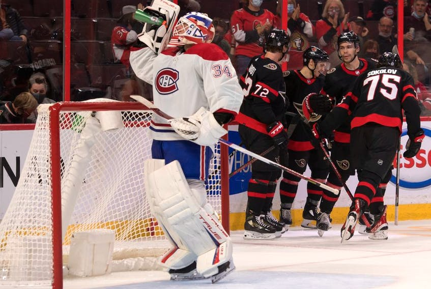 Canadiens goaltender Jake Allen quenches his thirst while Senators players celebrate a second-period goal by Egor Sokolov at the Canadian Tire Centre in Ottawa Friday night.