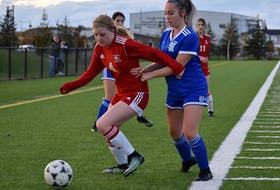 Eve Somers of the Riverivew Ravens, left, protects the ball as she's pressured by Ava Marks of the Sydney Academy Wildcats during Cape Breton High School Soccer League girls' playoff action at Open Hearth Park in Sydney, Tuesday. Riverview won the game 2-0, eliminating Sydney Academy from championship contention. JEREMY FRASER/CAPE BRETON POST.