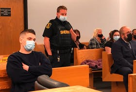 Brandon Noftall (left) sits in a provincial courtroom in St. John's Wednesday, Oct. 20, prior to the start of his preliminary hearing on charges of second-degree murder, assault and court order breaches. Noftall is accused of killing his stepfather, Bobby Noftall, last December. Seated to the right are Bobby Noftall's loved ones.